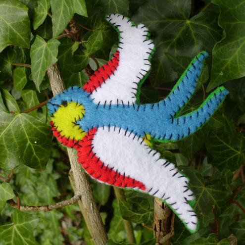 Broche o decoración de fieltro con forma de pájaro en pleno vuelo
