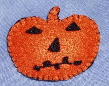 Broche o adorno de fieltro de una calabaza para Halloween