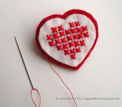 Broche de fieltro con forma de corazón con punto de cruz