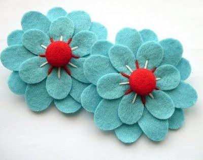 Bonita flor de fieltro con pétalos en turquesa y rojo