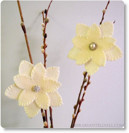 Jarrón decorado con ramas secas y flores blancas de fieltro