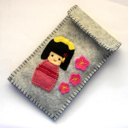 Funda de móvil de fieltro con una Kokeshi doll
