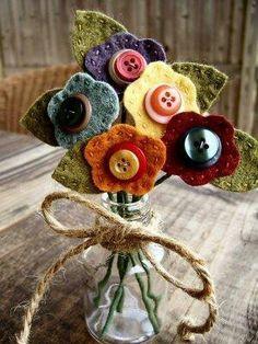 Jarrón de cristal con un ramo de flores de fieltro y botones